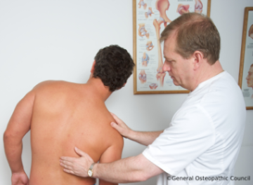 Osteopath examining spine